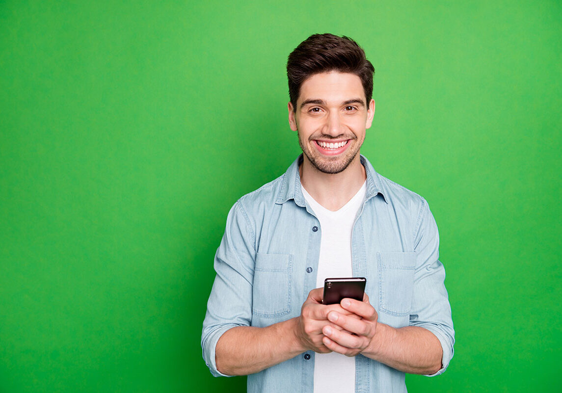 Photo of cheerful brown haired handsome blogger browsing through his telephone, looking for ideas to post in his social media isolated over green vivid color background