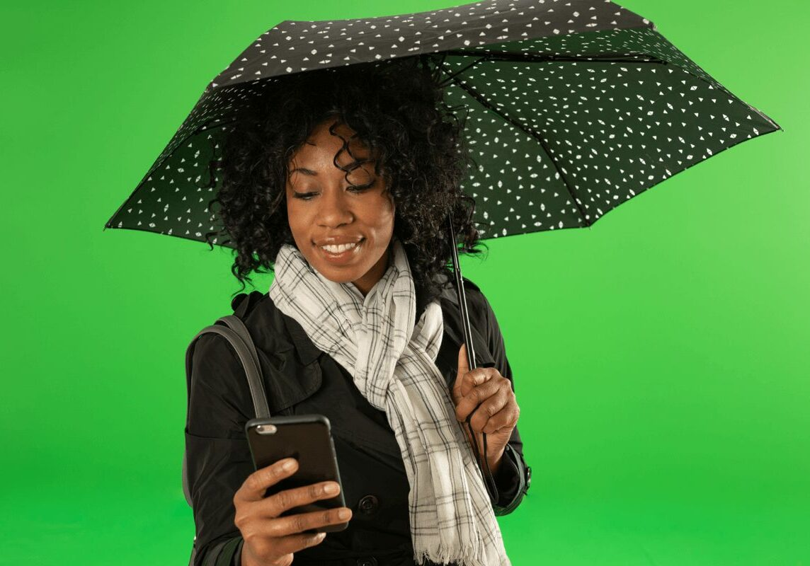 woman under umbrella looking at phone