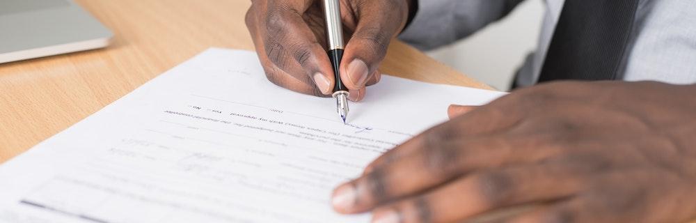 A man signs official paperwork.